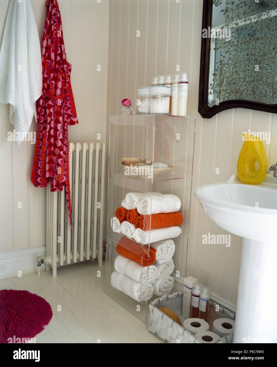 Rojo de albornoz y toalla blanca en la pared arriba del radiador en chapa blanca baño con toallas en estanterías de metacrilato Foto de stock