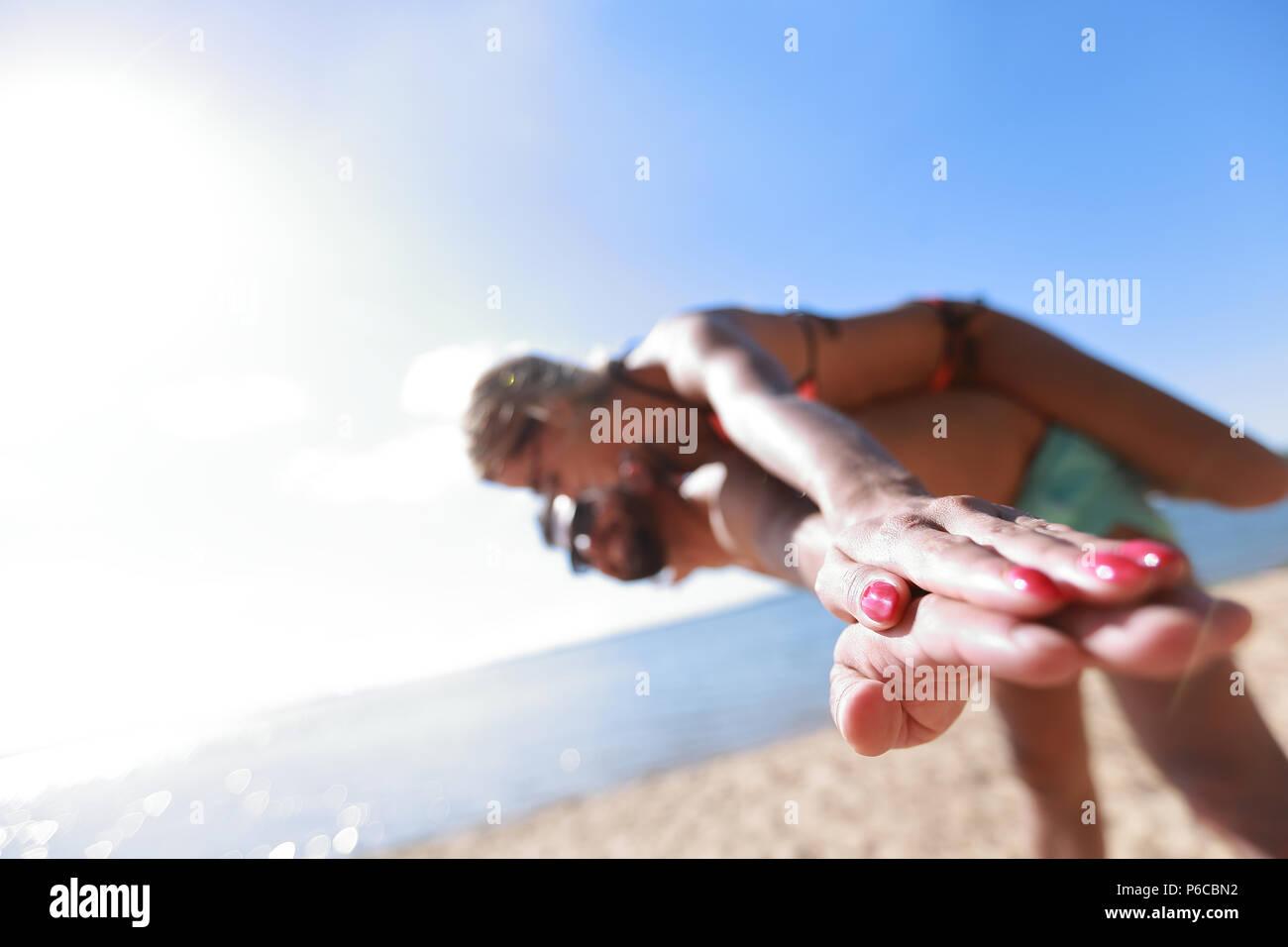 El hombre lleva una mujer piggyback en la playa. Imagen De Stock