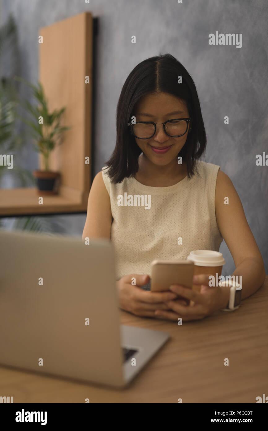 Embarazada empresaria a través de teléfono móvil en el escritorio Foto de stock