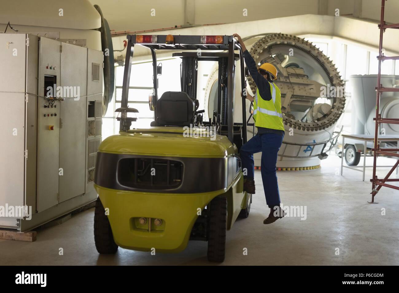 Trabajador masculino obteniendo en carretilla elevadora Imagen De Stock