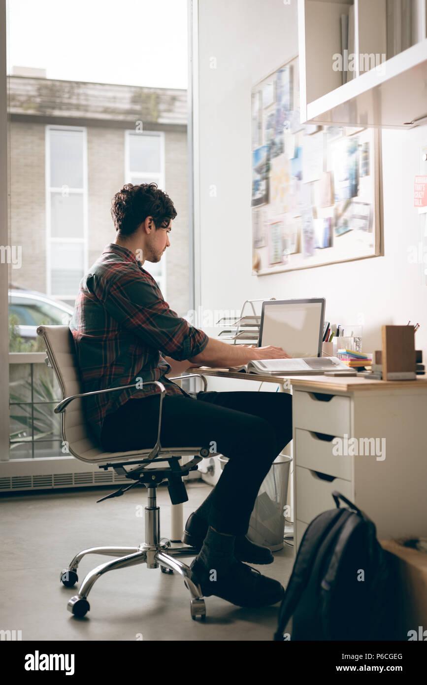 Ejecutivo que trabaja en un portátil en la oficina Foto de stock