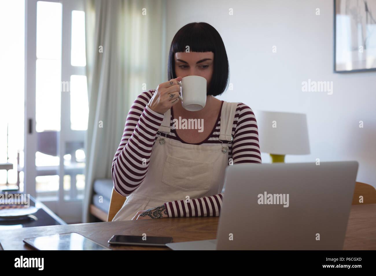 Mujer con café mientras usa portátil en casa Foto de stock