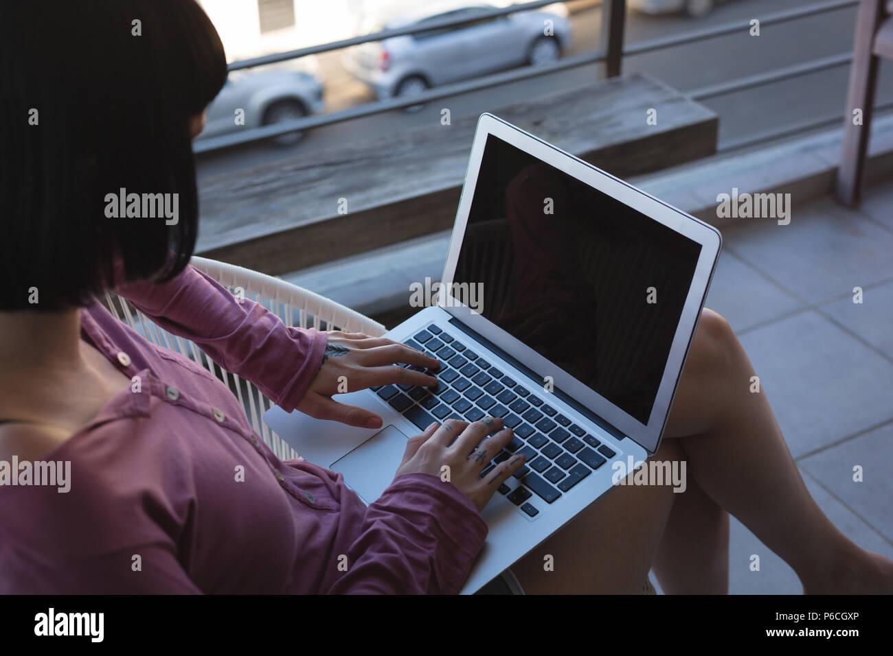 Mujer con portátil en el balcón Foto de stock
