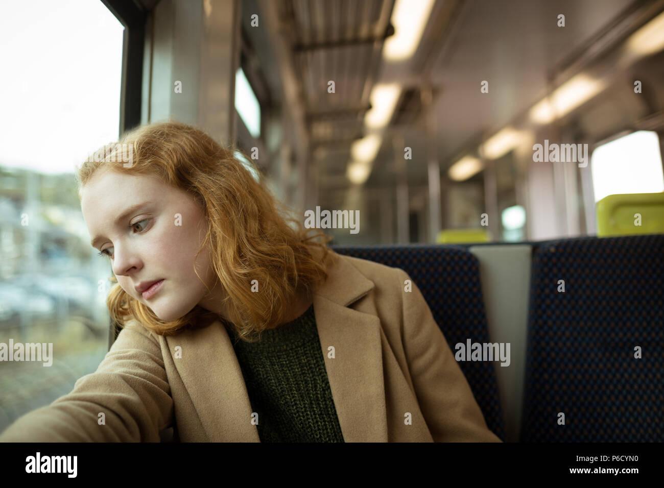 Cabello rojo joven mirando fuera de la ventana Foto de stock