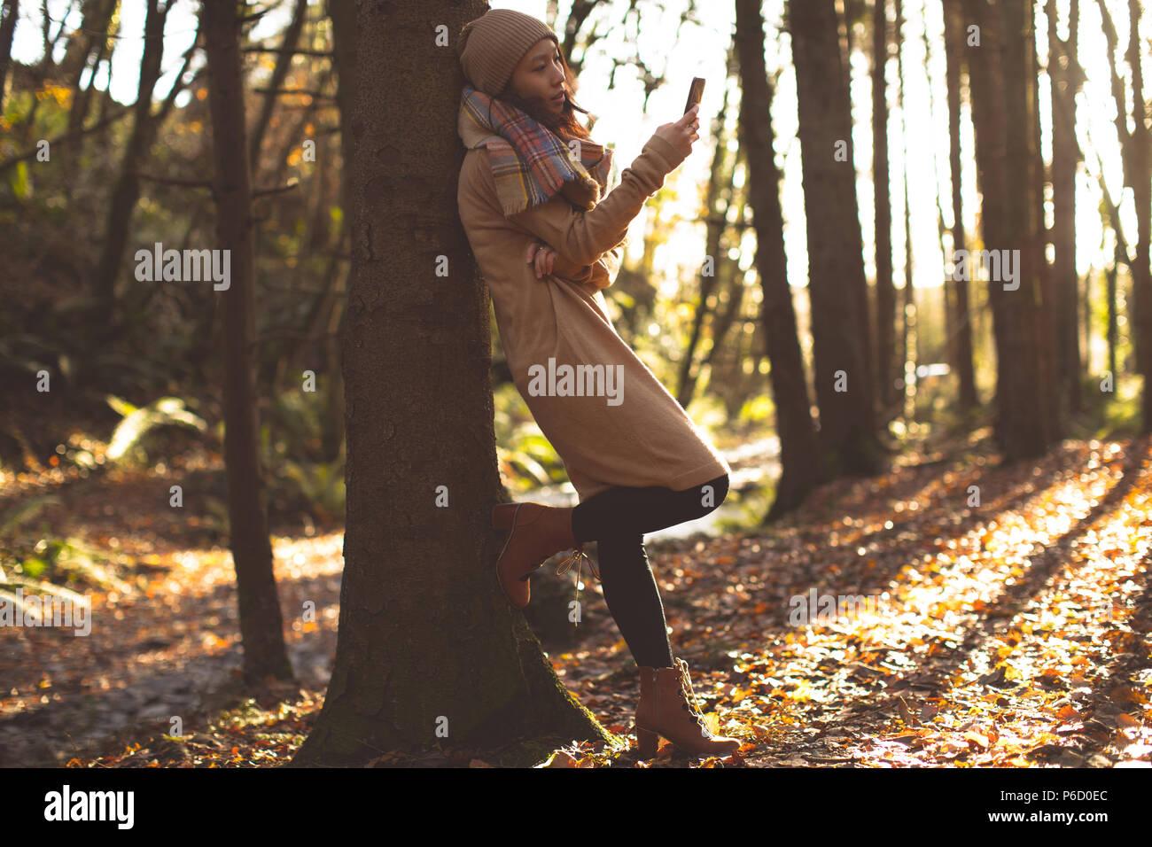 Bella mujer en ropa de abrigo a través de teléfono móvil Foto de stock