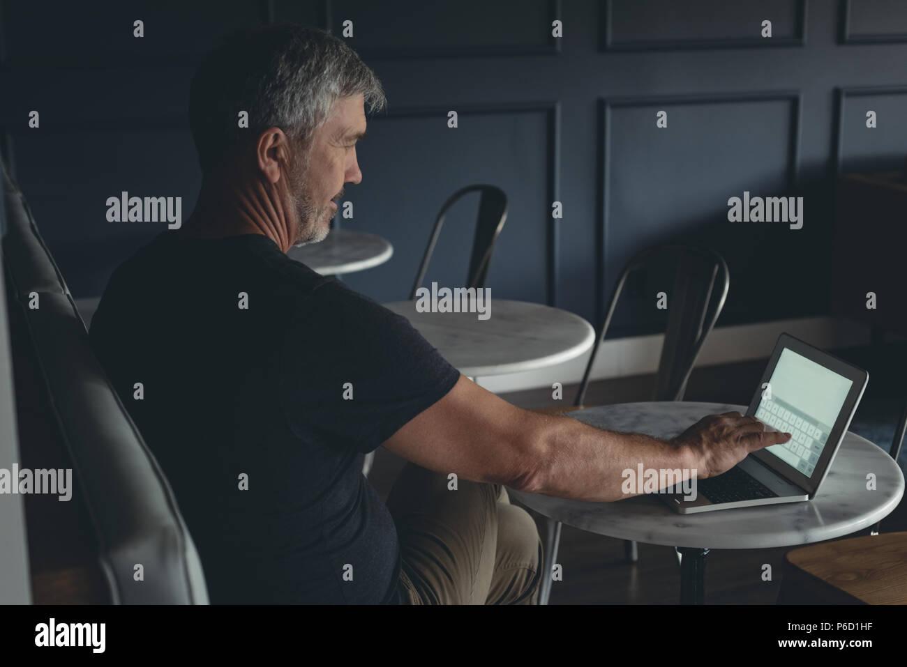 Empresario utilizando el portátil en la cafetería Foto de stock