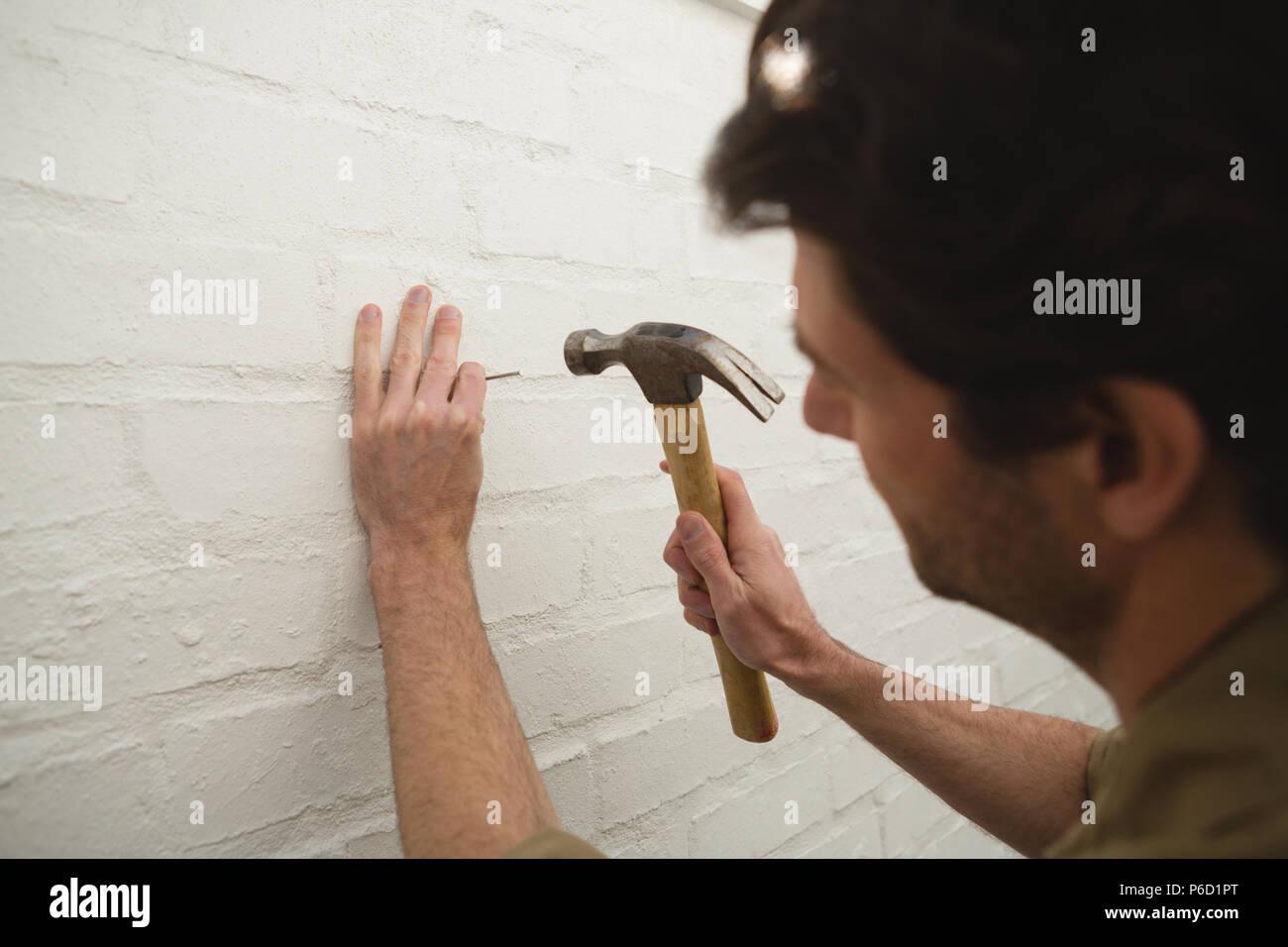 Carpintero macho martillando clavos en la pared Foto de stock