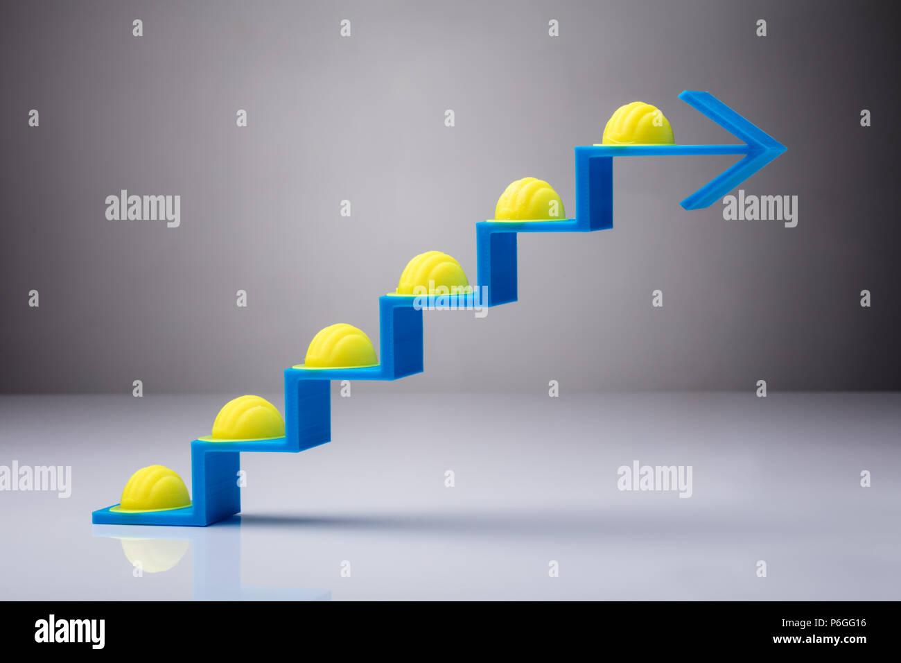 Muchos cascos amarillos en aumentar la flecha azul pasos sobre fondo blanco. Imagen De Stock
