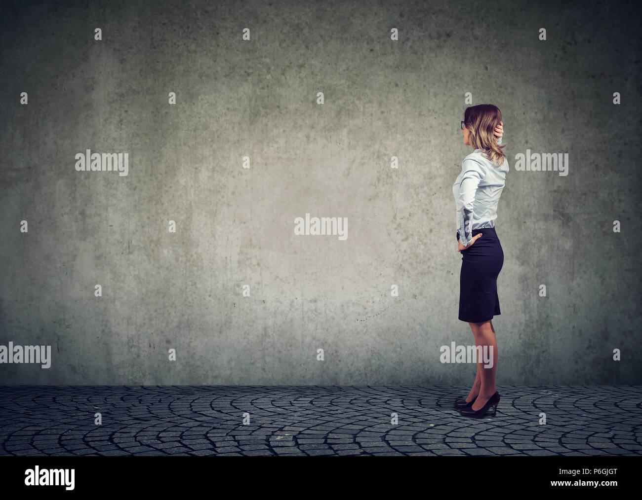 Vista lateral de la empresaria de pie en frente de la pared gris y contemplar en un esfuerzo para resolver el problema Imagen De Stock