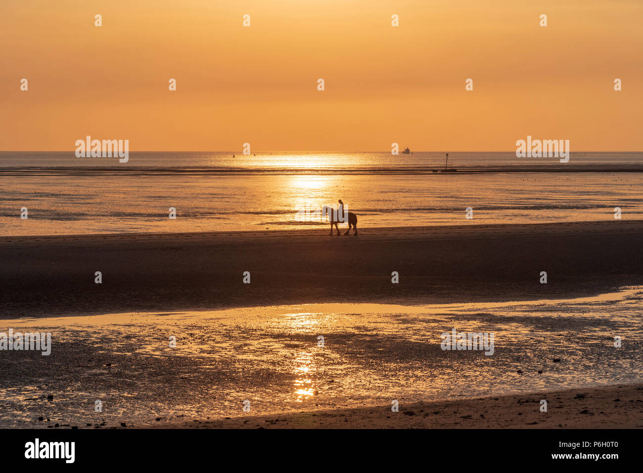 La puesta de sol. Crosby beach. Liverpool, Noroeste de Inglaterra. Jinete solitario. Imagen De Stock