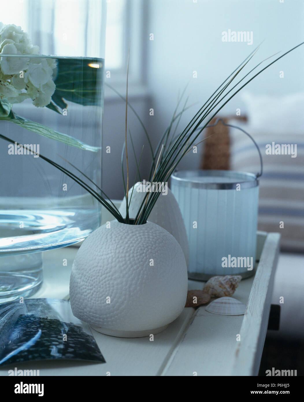 Cerca de pastos en jarrón de cerámica circular blanco sobre blanco tabla Foto de stock