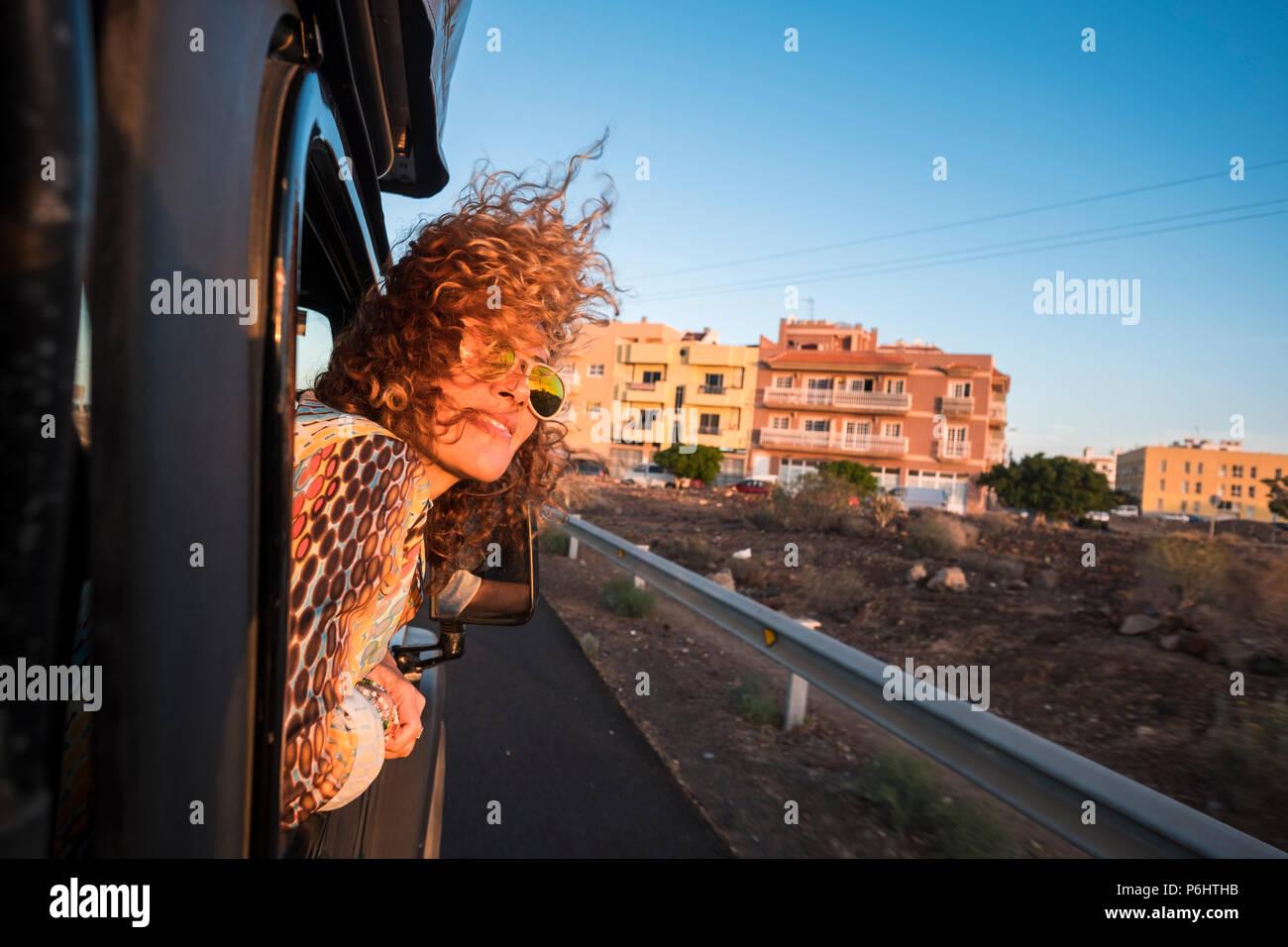 Hermosa dama caucásicos con bonita sonrisa viajar en un coche negro mirando el sol del atardecer y disfrutar de la cálida temporada. El horario de verano para el modelo viajar wi Foto de stock