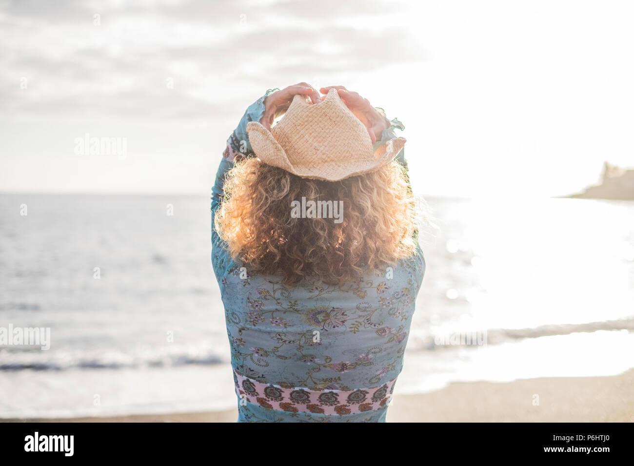 Mujer joven con libertad cowboay sombrero en frente del océano disfrutando de las vacaciones y el estilo de vida al aire libre. La luz solar del verano y las olas y espíritu viajero Imagen De Stock