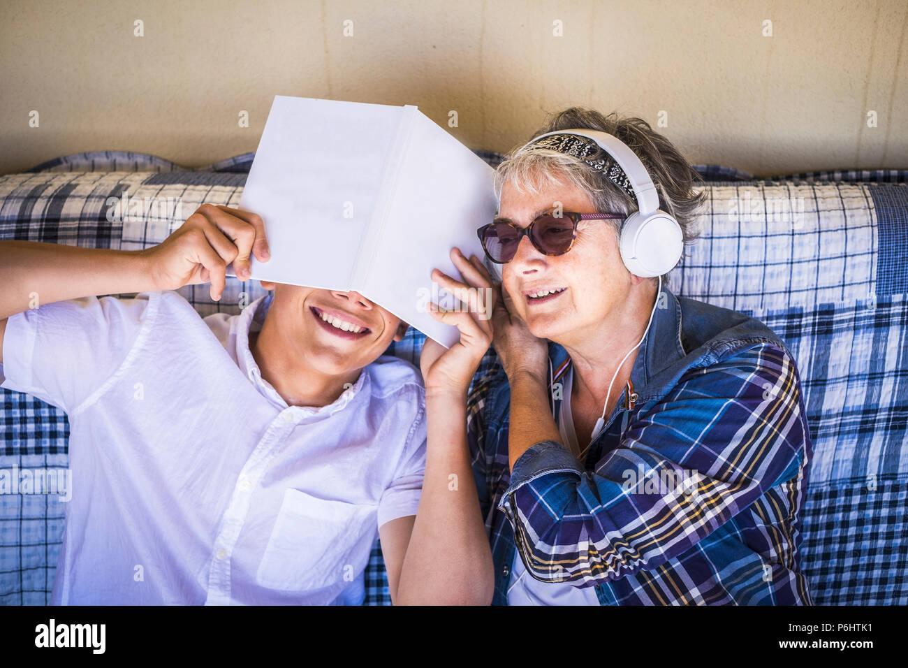 Par de personas felices disfrutando del verano el tiempo libre juntos en la terraza al aire libre. el joven no quiere estudiar mientras la abuela liste Imagen De Stock