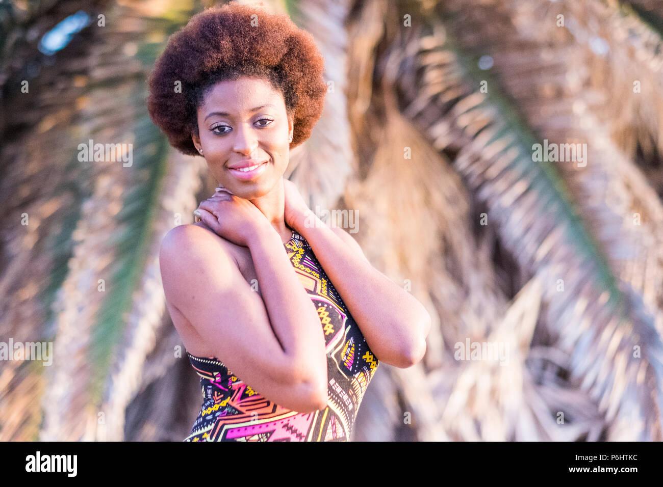 Lindo alegre niña modelo afro africano posan en un lugar tropical. El horario de verano y de esparcimiento para la joven y bella mujer sonriente bajo el sol con Imagen De Stock