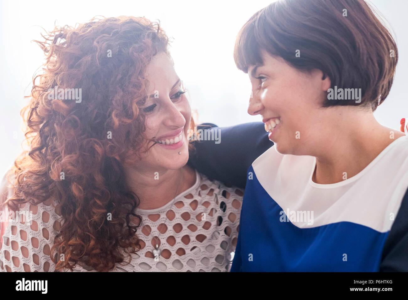 Par de amigas sonriendo juntos mutuamente. Disfrute y relación. friendshiop hermosas jóvenes caucásicos con fondo blanco. Imagen De Stock
