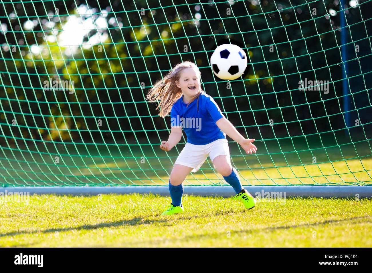 Los niños juegan al fútbol en el campo al aire libre. Los niños un gol bef43719a407c
