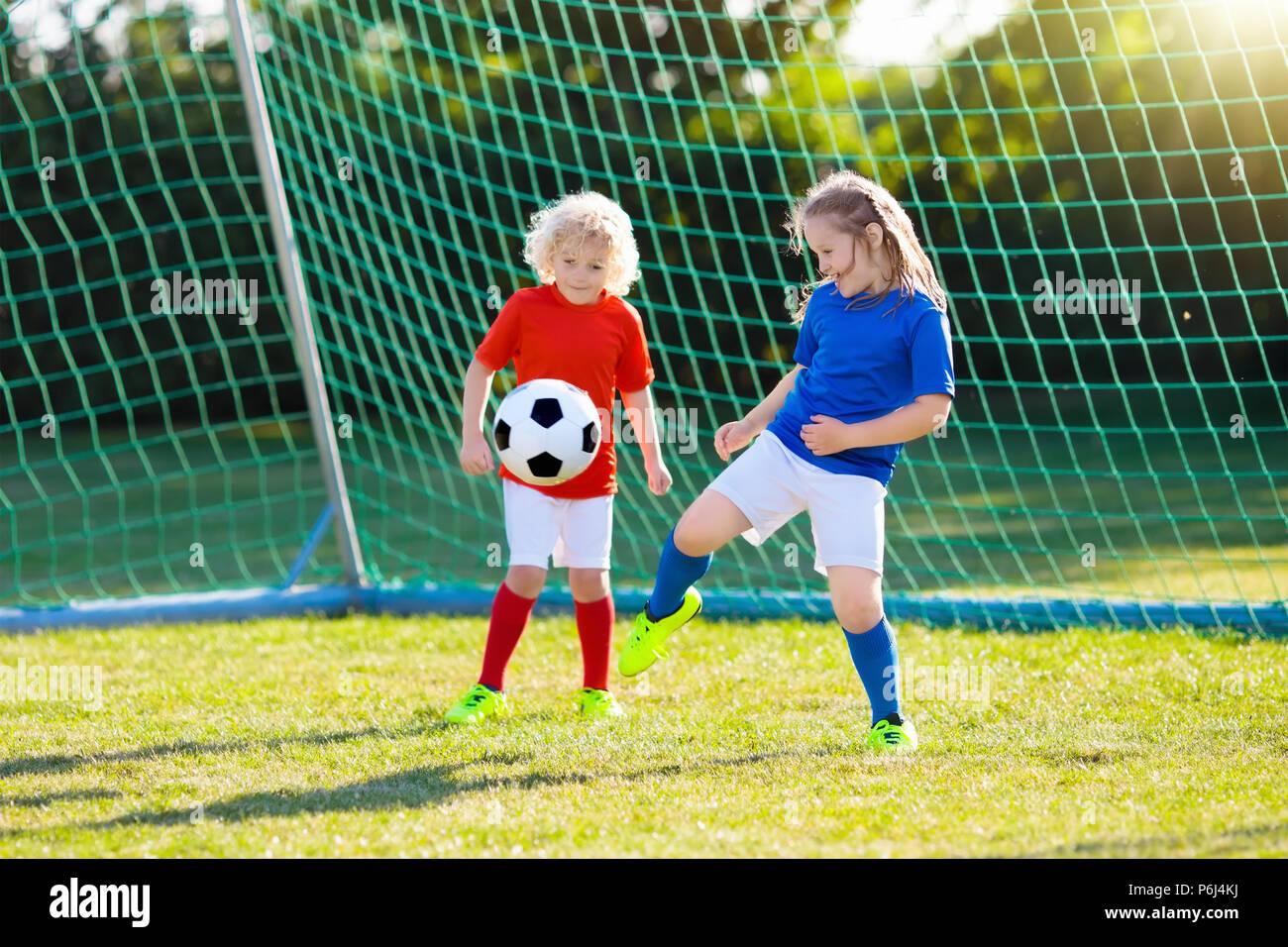 Los niños juegan al fútbol en el campo al aire libre. Los niños un gol en  el partido de fútbol. Niños y niñas patear la pelota. Niño corriendo en el  equipo ... 010fa6fc8c873