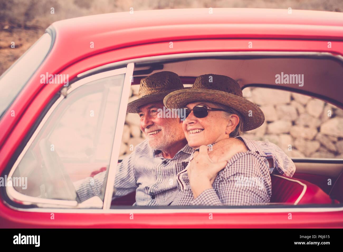 Pareja de ancianos con sombrero, con gafas, con el pelo blanco y gris, con camisa casual, en vintage coche rojo en vacaciones disfrutando de tiempo y vida. Con un chee Imagen De Stock
