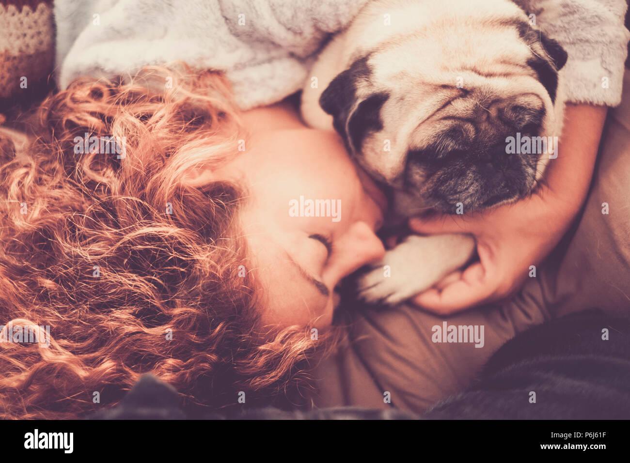 Verdadero amor verdadero entre la mediana edad hermosa mujer caucásica durmiendo y proteger sus mejores amigos perro pug. La amistad y las relaciones en el hogar en el Imagen De Stock