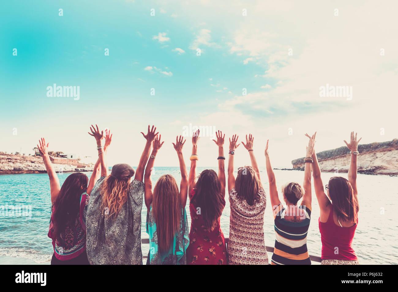 Grupo de mujeres disfrutando de las vacaciones de verano y celebrar todos juntos diciendo hola al océano y la naturaleza. los jóvenes, actividades de ocio, todas las manos Imagen De Stock