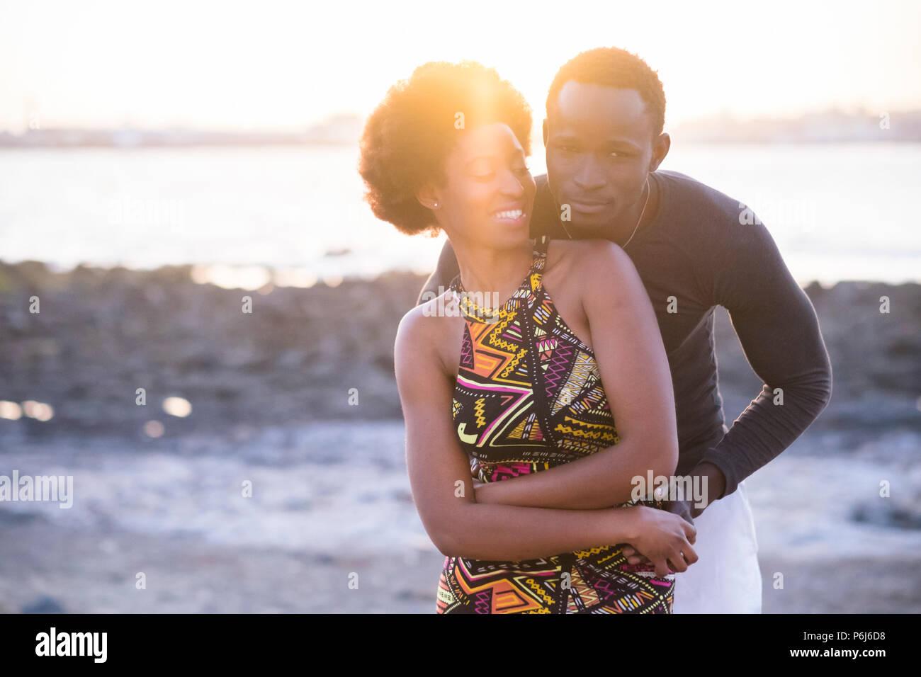 Hermoso par de raza negra modelos africanos en traje tradicional divertirse y amor junto a la playa en verano, durante el atardecer de retroiluminación de Niza. Imagen De Stock
