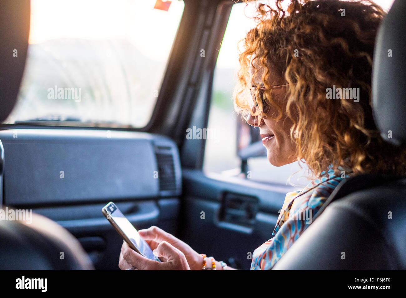 Hermosa dama caucásica edad media watch smartphone para controlar los medios sociales en Internet y encontrar amigos. leer mensajes utilizando la tecnología wifi mientras tra Foto de stock
