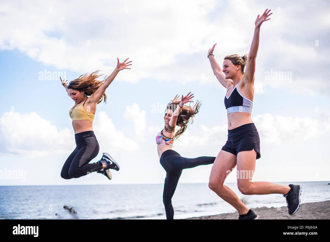 Tres hermosas bodí cacuasian niñas saltando en la playa haciendo ejercicio. fintess actividad deportiva al aire libre para el grupo de mujeres personas con oceaní Imagen De Stock