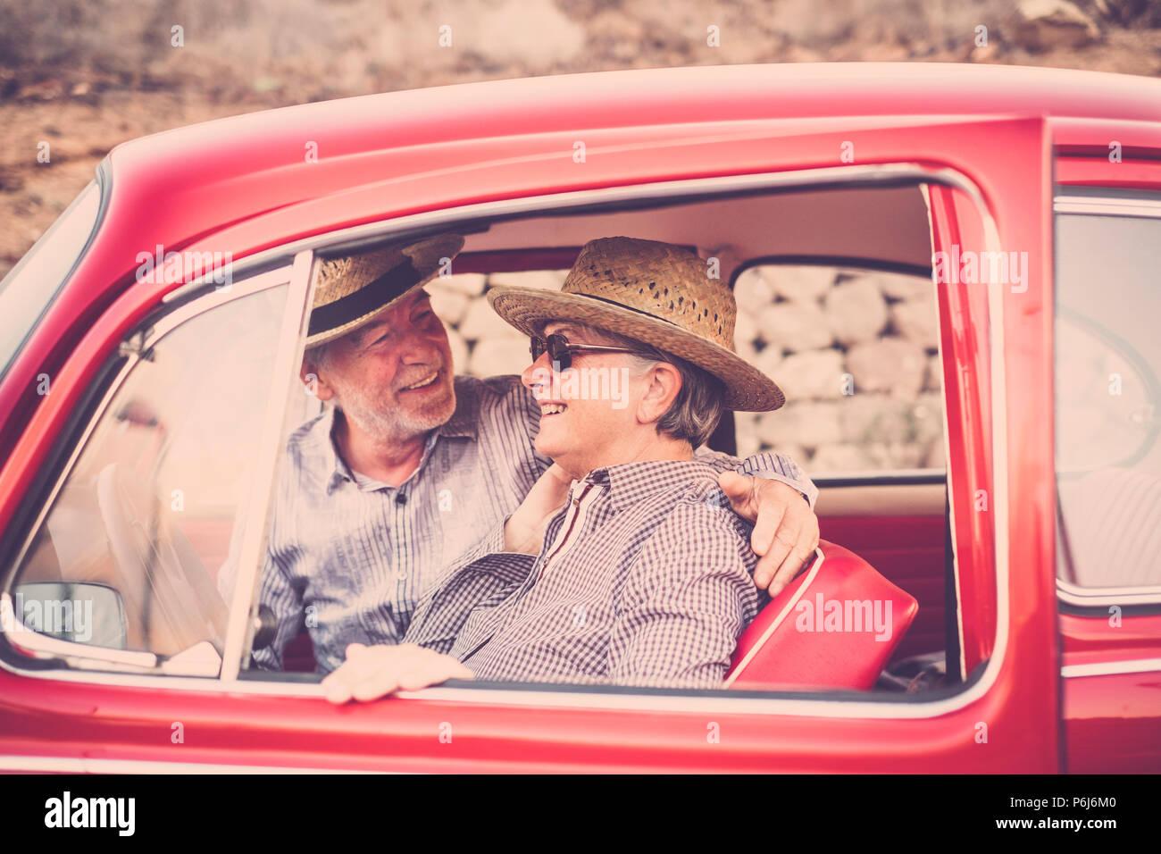 Bonito Hermoso par de altos personas adultas dentro de un viejo coche vintage rojo disfrutar y permanecer juntos en viajes al aire libre actividad de ocio. Casado y para Imagen De Stock