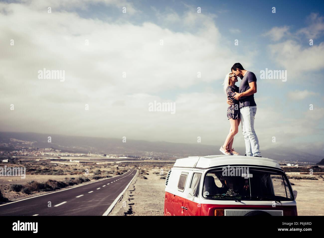 Hermosa pareja caucásica en el amor de pie sobre el techo de una vendimia legendaru van. Viajes y concepto de familia. largo camino asfaltado en el fondo y el cielo Imagen De Stock