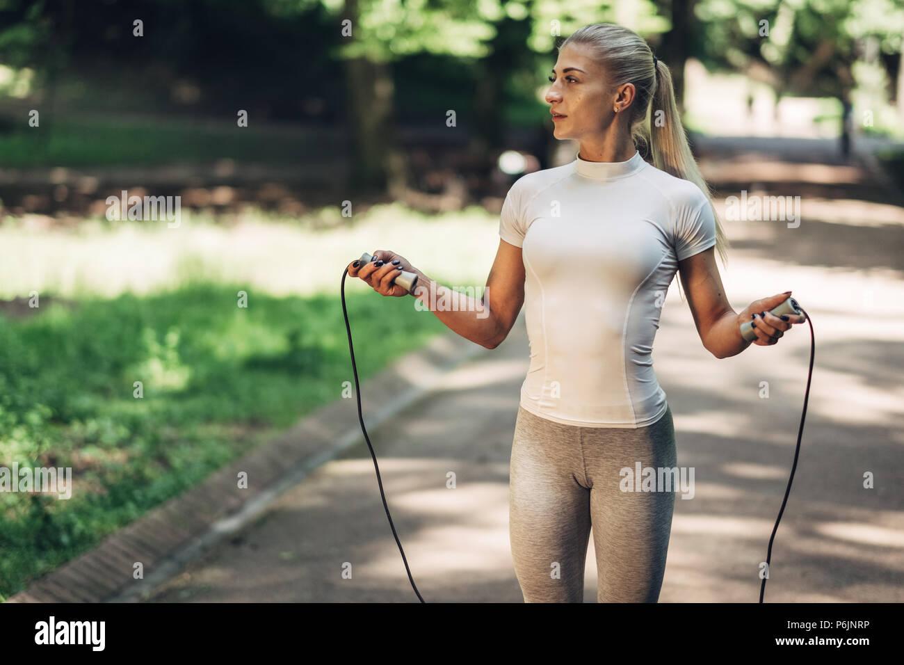 Colocar el retrato de mujer joven con saltar la cuerda en el parque.  Fitness femenino haciendo ejercicio al aire libre en el parque el día  soleado. 5ce9fd390fa