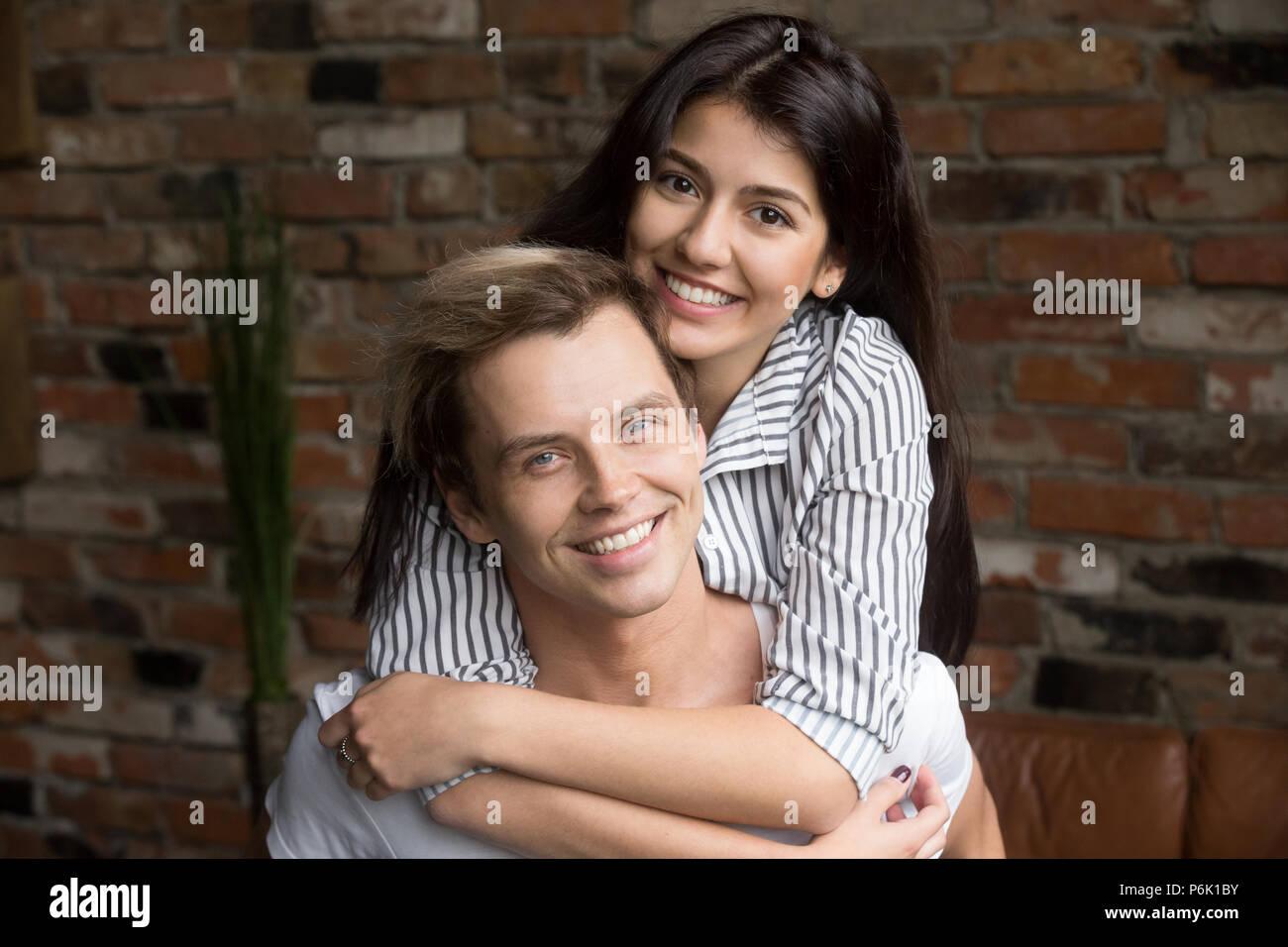 Retrato de la feliz pareja milenaria abrazando posando para familia al. Imagen De Stock