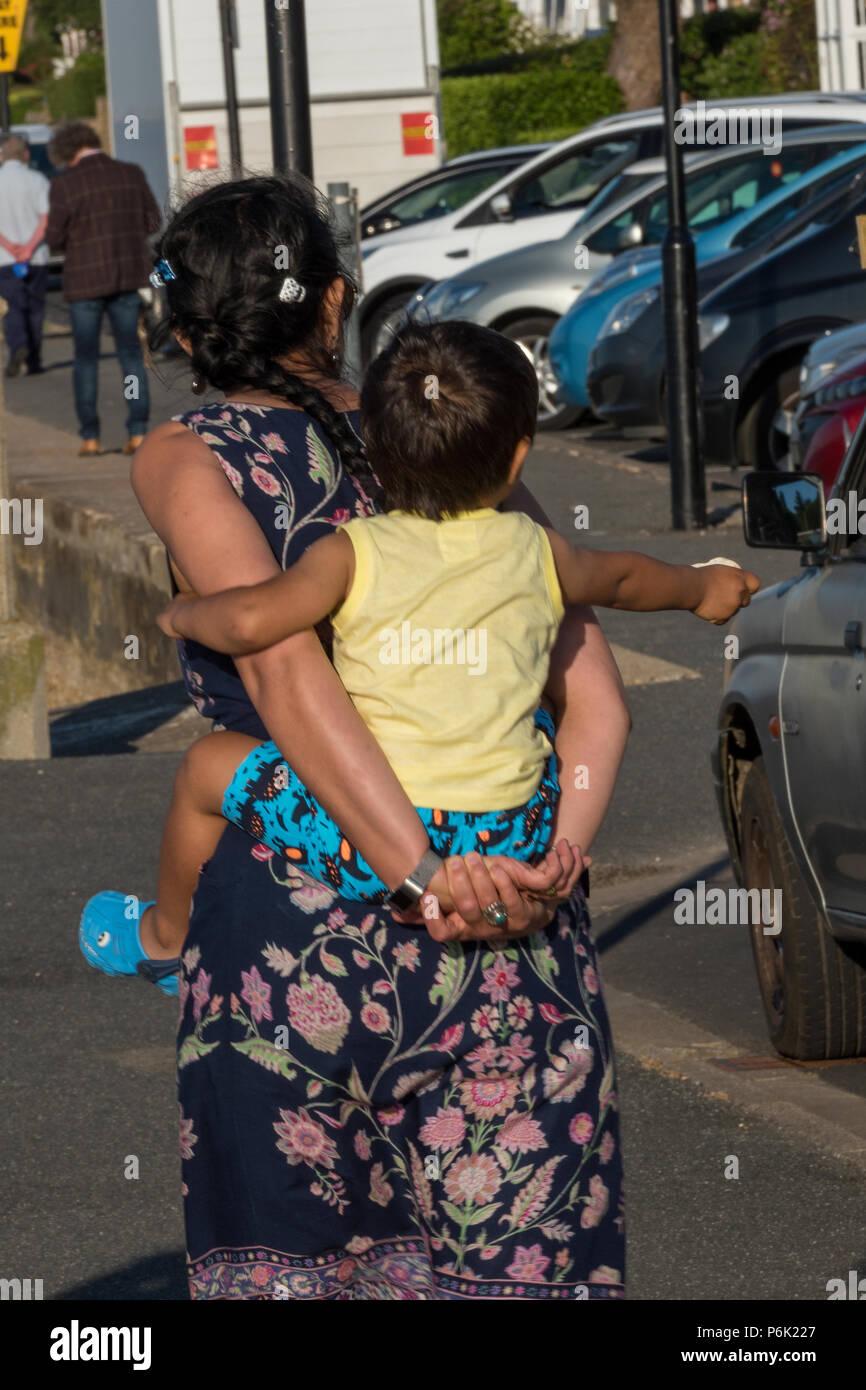 Mujer que llevaba el bebé sobre su espalda, piggy back. Imagen De Stock