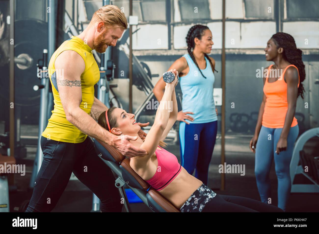 Vista lateral de un guapo entrenador personal guía a su cliente en el gimnasio Imagen De Stock