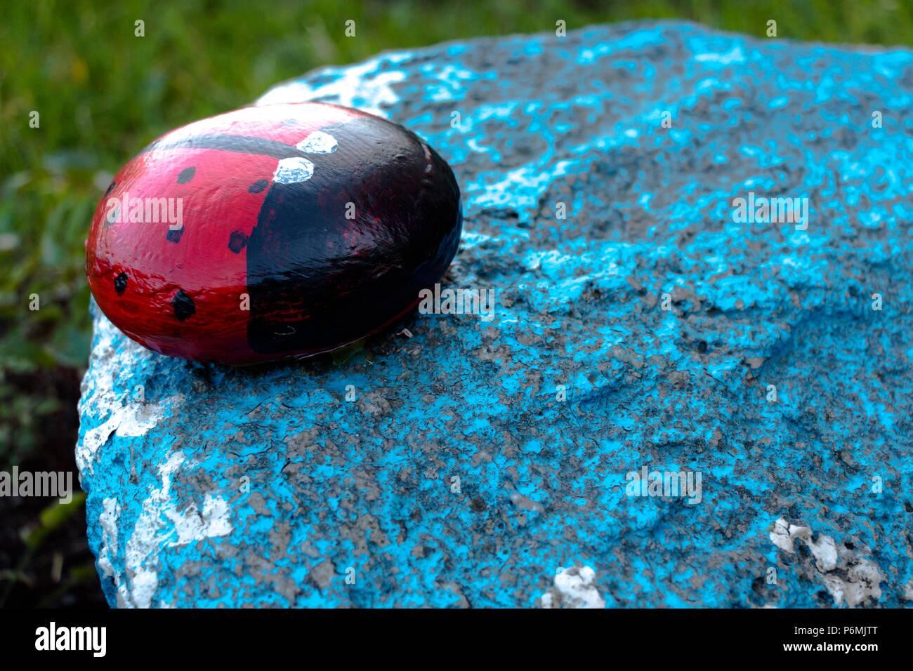 Un insecto llamado mariquita está hecha de piedra y pintado de sus tintas. La cifra se sitúa en el jardín en una piedra azul. Muy bonito e interesante h Foto de stock