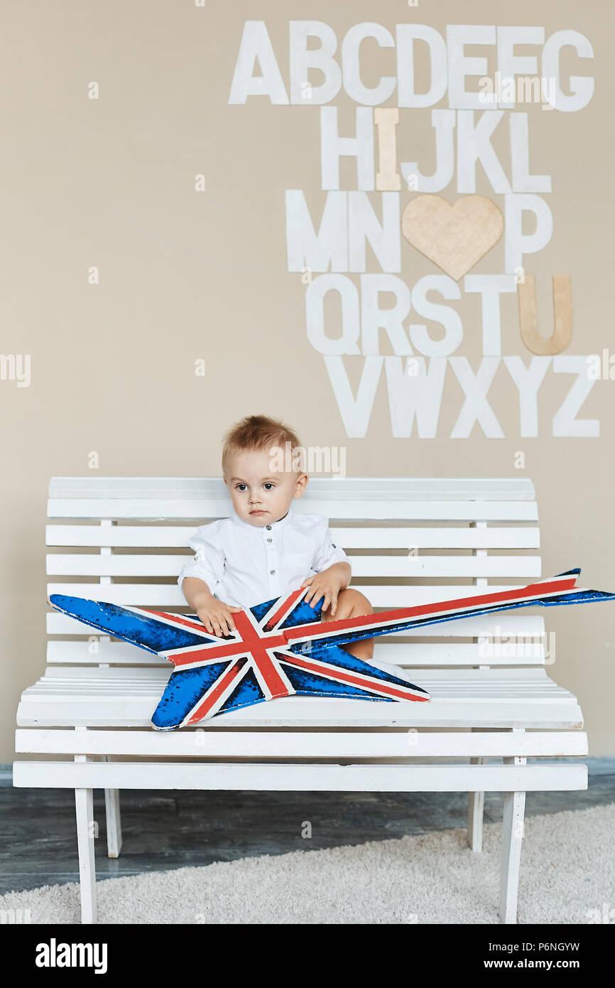 Gracioso niño con rock rock guitar, moda Little Baby Boy con la camisa blanca se sienta en un banco y posando en studio Imagen De Stock