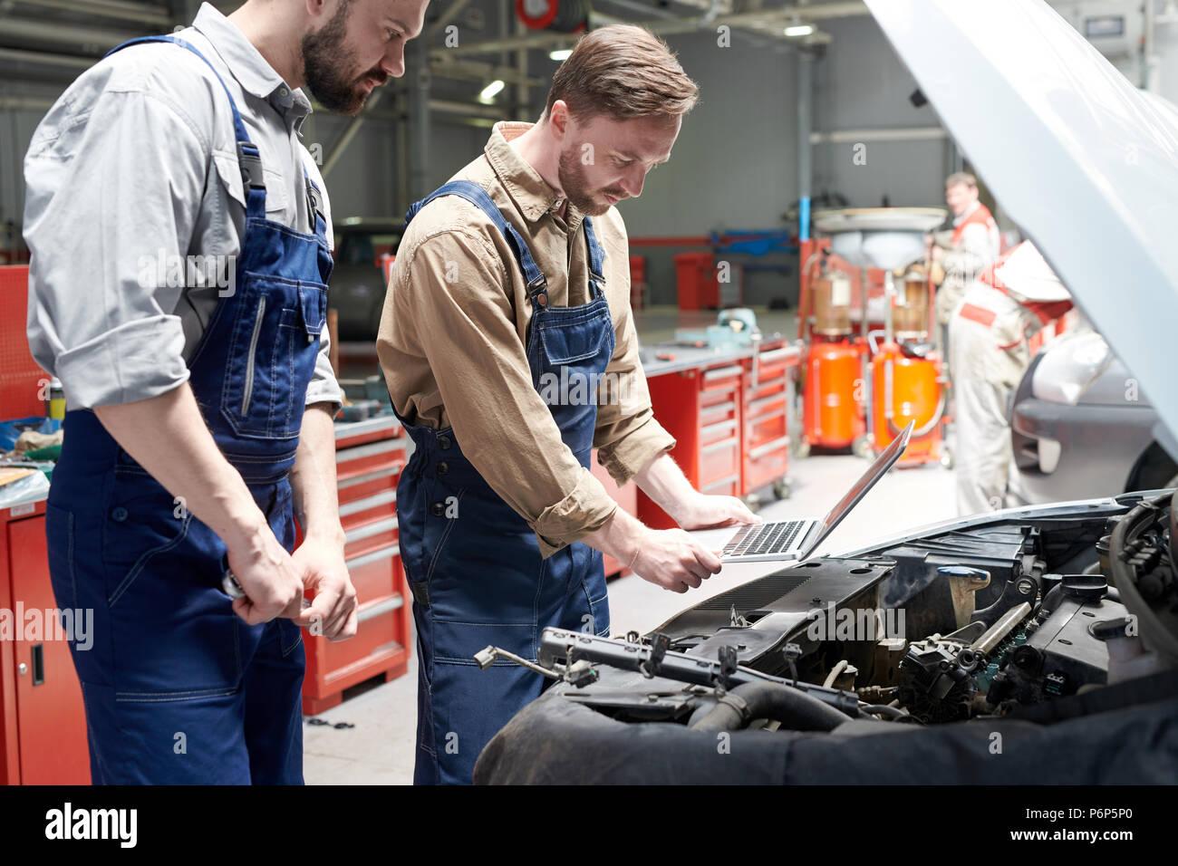 Dos mecánicos inspección de coche Imagen De Stock
