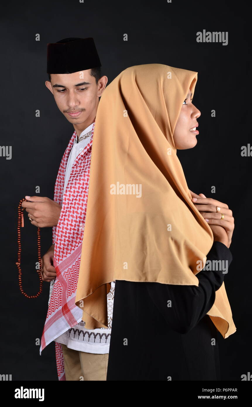 Los jóvenes musulmanes, hombres y mujeres orando Imagen De Stock