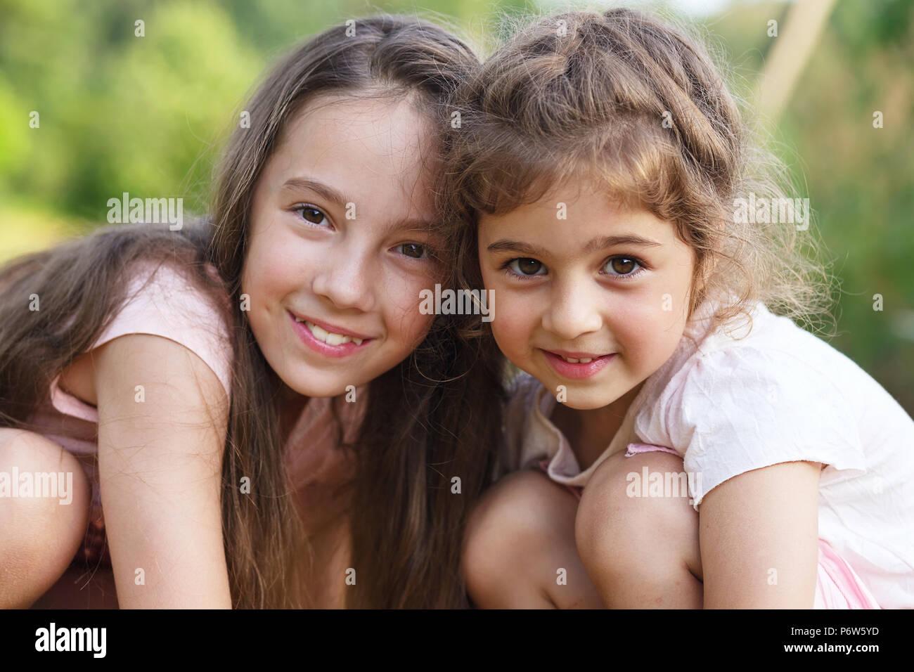 Dos niñas feliz abrazando al verano park Imagen De Stock