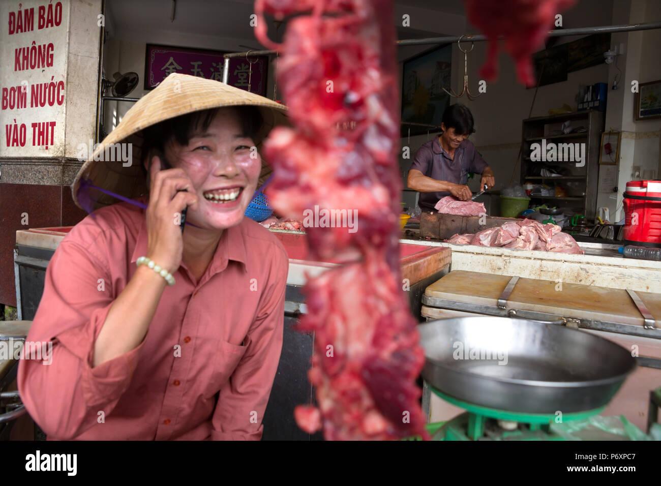 Mujer carnicero vendiendo carne y por teléfono con sombrero cónico en Can Tho, Vietnam Foto de stock