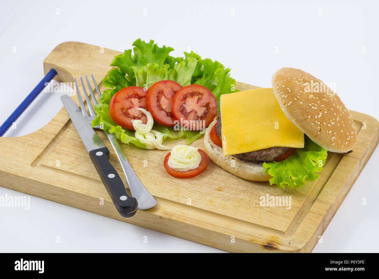 Hamburguesa casera con lechuga, tomate, queso, carne de res y papas fritas colocadas sobre fondo de madera , frescos sabrosas hamburguesas, de fondo Foto de stock