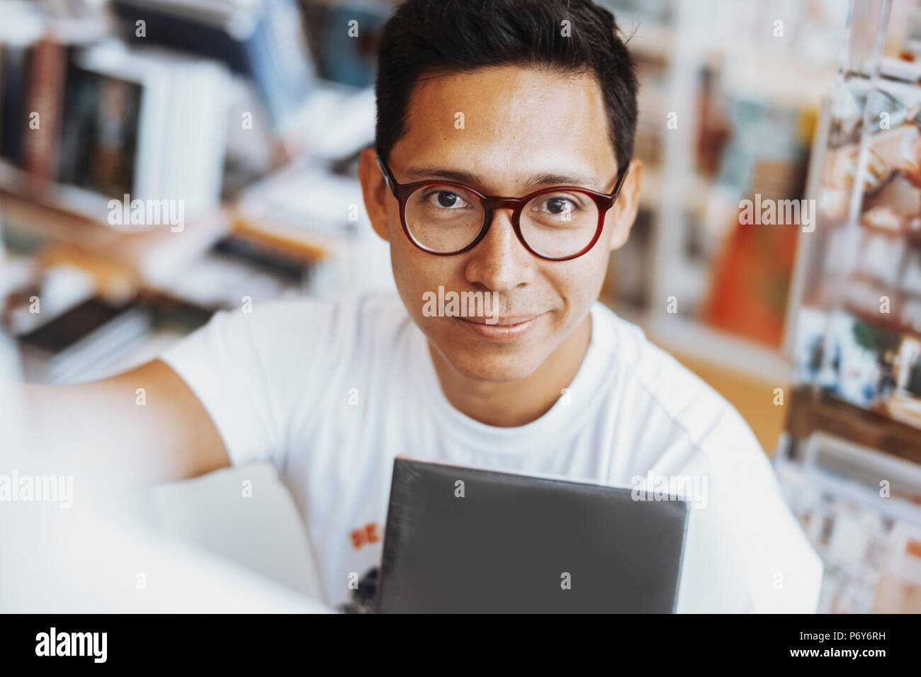 Atractiva joven oso hombre sonriendo y celebración de libro en las manos. Imagen De Stock