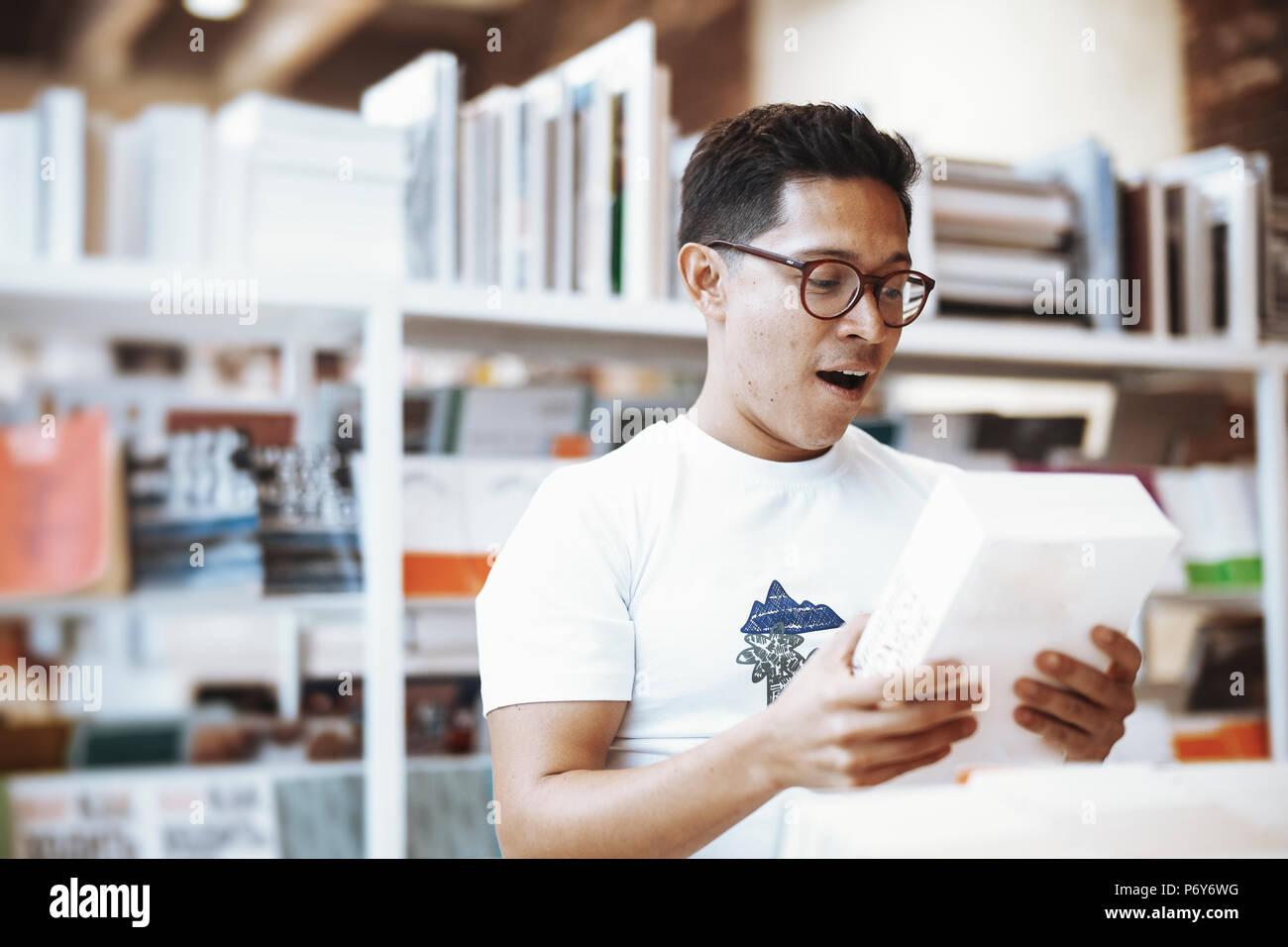 Oso atractivo joven hombre con libro y demostrar sorprendido rostro. Foto de stock