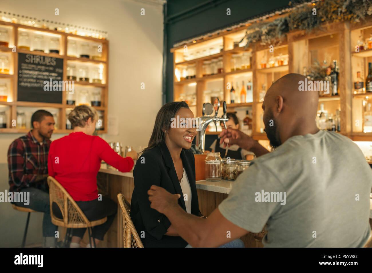 Sonriente pareja americana africana juntos y disfrutar de una copa en un bar. Imagen De Stock