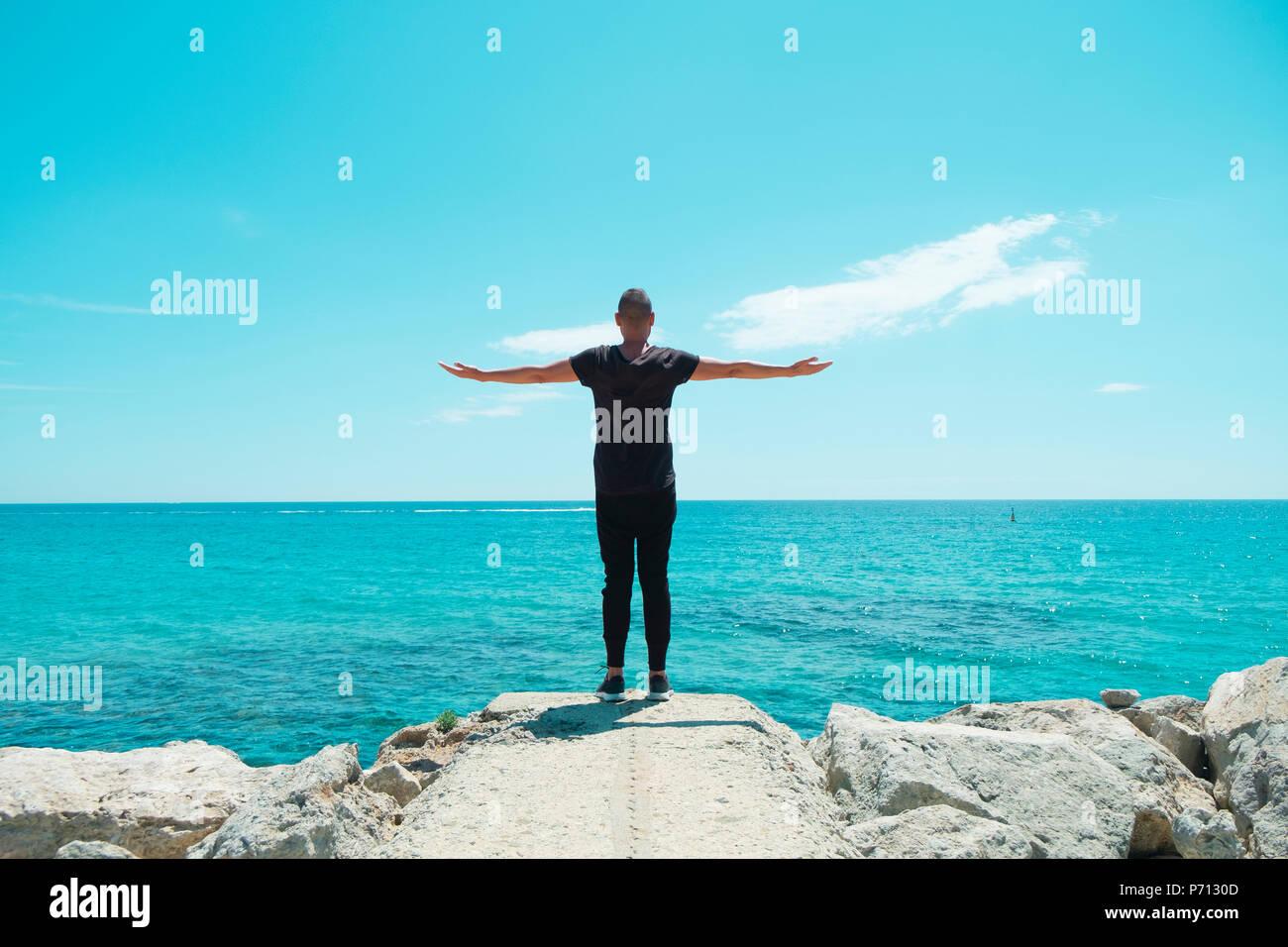 Un joven hombre negro caucásico, vistiendo pantalones de sudadera y una camiseta negra, visto desde atrás con sus brazos en el aire delante del océano, sintiéndose libre Imagen De Stock