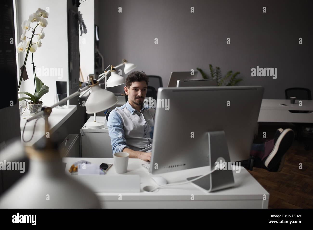 Joven Hombre Barbado inteligente trabajando en loft moderno studio-ofi Imagen De Stock