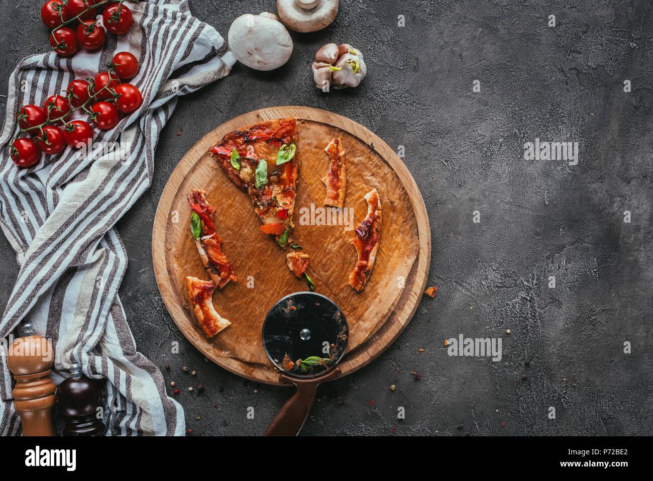 Vista superior de pedazos de comer pizza con cortador de hormigón tabla Imagen De Stock