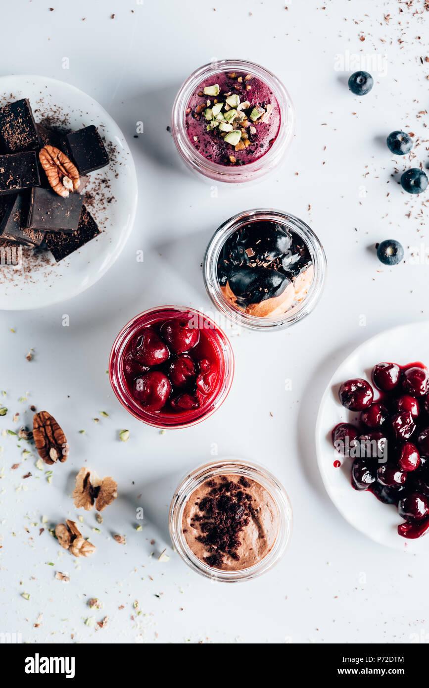 Vista superior de diversos dulces deliciosos postres en tarros de vidrio Imagen De Stock