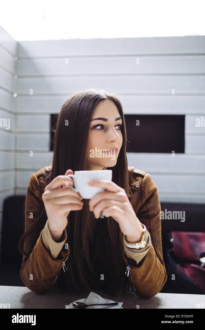 Bonita morena joven sentado en el cafe bar y bebiendo café. Imagen De Stock