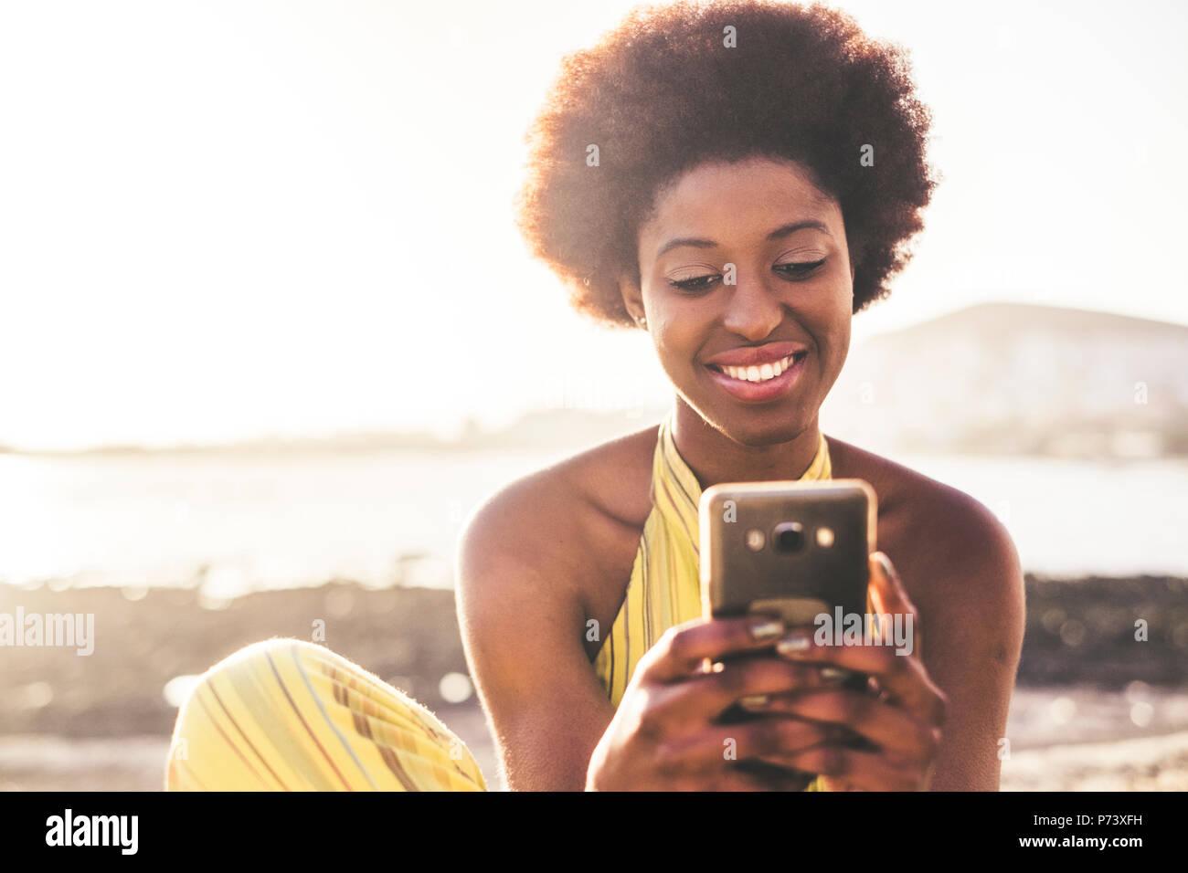 Hermosa chica joven modelo negro cabello africano rac utiliza tecnología de telefonía móvil para escribir amigos durante las vacaciones. Ocean y retroiluminación en el fondo, o Imagen De Stock